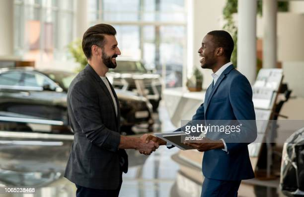 customer closing a deal with a salesman at a car dealership - showroom stock pictures, royalty-free photos & images