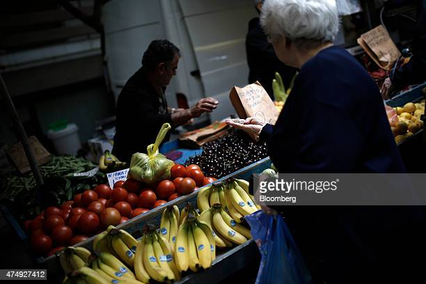 A customer collects her change in euro coins after paying a trader for fresh groceries at a farmer's market on Kassandrou street in Thessaloniki...