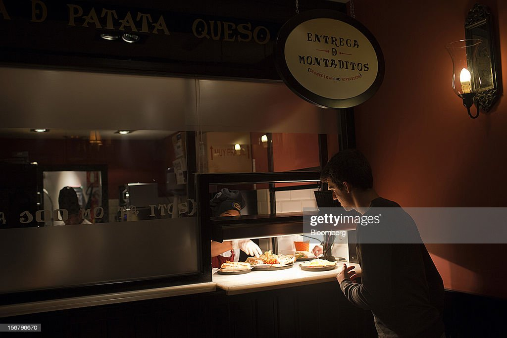 A customer collects his food order from the counter at a 100 Montaditos restaurant in Madrid, Spain, on Wednesday, Nov. 21, 2012. The Madrid-based chain in January opened its first U.S. restaurant in Miami and aims to have eight outlets in Florida by next March. Photographer: Angel Navarrete/Bloomberg via Getty Images