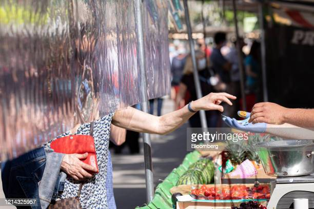 A customer collects their euro currency change under a protective cellophane screen on a fruit and vegetable market stall at Marche SaxeBreteuil in...
