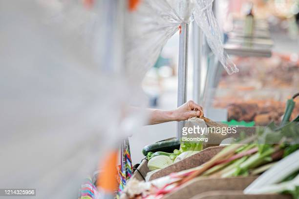 A customer collects their fresh produce under a protective cellophane screen on a fruit and vegetable market stall at Marche SaxeBreteuil in Paris...