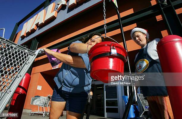 A customer coming out of a WalMart store donates to the Salvation Army as bell ringer Karrie Stasson watches on December 17 2004 in Anaheim...