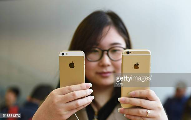 A customer compares rose gold iPhone SE and iPhone 6S at an Apple Store on March 31 2016 in Hangzhou Zhejiang Province of China Apple launched a new...