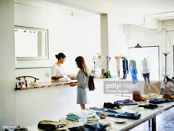 customer completing transaction on digital tablet - image stock pictures, royalty-free photos & images