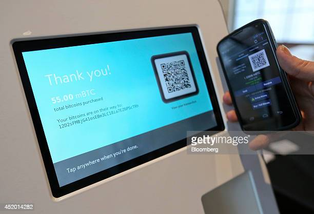 A customer confirms receipt of a bitcoin purchase with cash using a bitcoin automated teller machine at the CoinSummit Virtual Currency conference in...