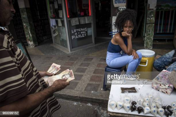 A customer counts 100 Bolivar banknotes before purchasing bagged portions of coffee and sugar at a stand in the Petare slum of Caracas Venezuela on...