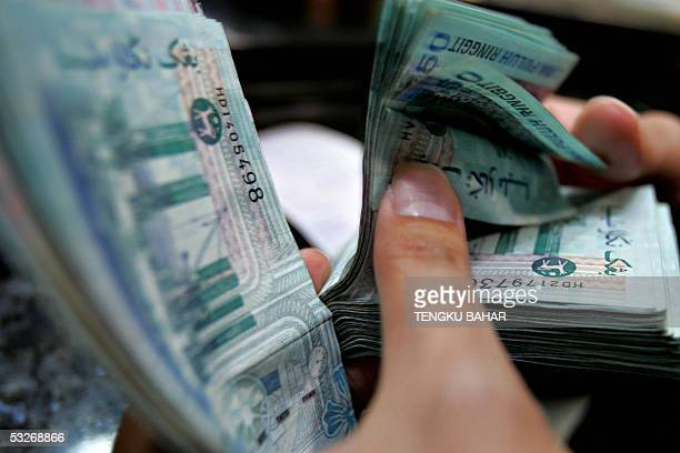 A customer counts a wad of 50 ringgit bills at the service window of a money changer in Kuala Lumpur 22 July 2005 The Malaysian ringgit was...