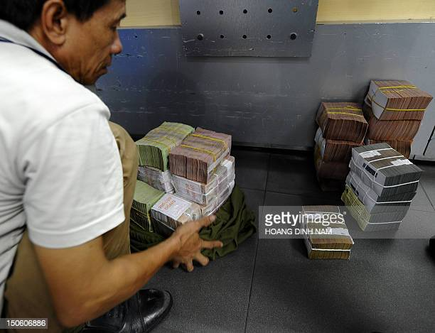 Customer counts dong bank notes after withdrawing cash at a local Asia Commercial Bank in Hanoi on August 23, 2012. Vietnamese stocks fell for a...