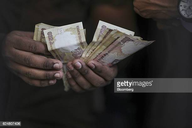 A customer counts five hundred and one thousand rupee banknotes for a photograph as he stands in line to exchange banknotes at a State Bank of India...