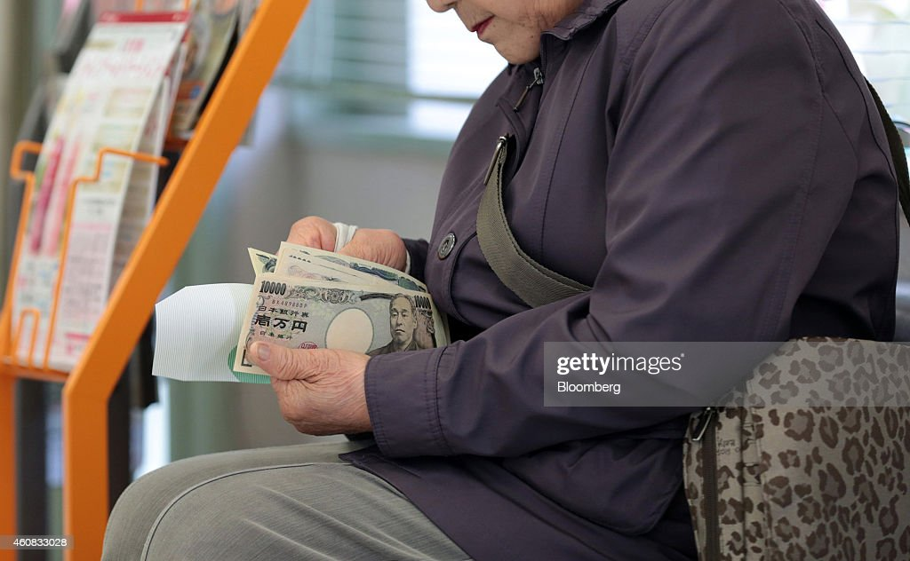 A customer counts her money after making a withdrawal at a  : News Photo