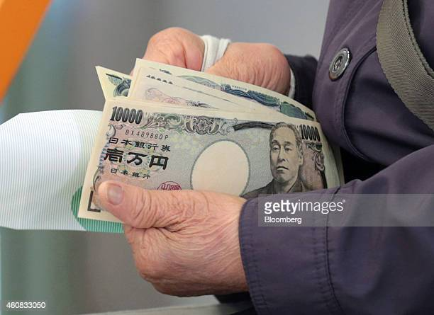 A customer counts her money after making a withdrawal at a Japan Post Co branch in Hachioji Japan on Tuesday April 15 2014 Companies are encouraging...