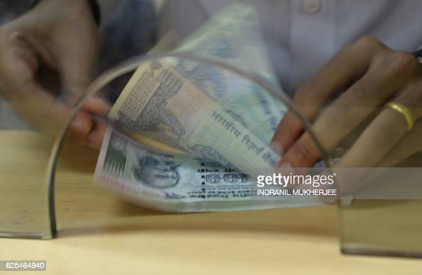 A customer counts Indian 100 rupee currency notes after withdrawing money at a bank on November 24 in the wake of the demonetisation of old 500 and...