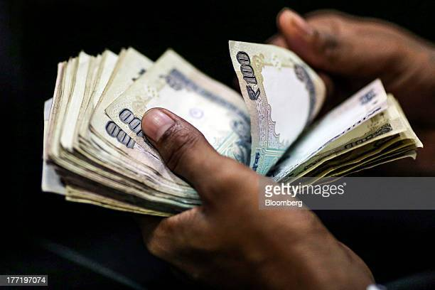 A customer counts Indian onehundred rupee banknotes before depositing them at a branch of the HDFC Bank Ltd in Mumbai India on Thursday Aug 22 2013...