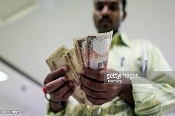 A customer counts Indian onethousand rupee banknotes before depositing them at a branch of the HDFC Bank Ltd in Mumbai India on Thursday Aug 22 2013...