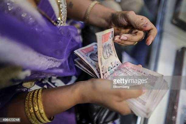 A customer counts Indian rupee banknotes at the Umedmal Tilokchand Zaveri jewelry store during the festival of Dhanteras two days before Diwali in...