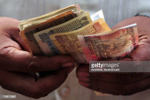 A customer counts Indian rupee currency notes received from a scrap dealer in Mumbai on August 19 2013 India's rupee hit a new low and shares slipped...
