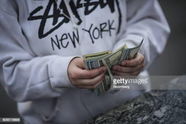 Customer counts money during the release of the Apple Inc. IPhone 7 and 7 Plus smartphones outside an Apple Inc. Store in New York, U.S., on Friday,...