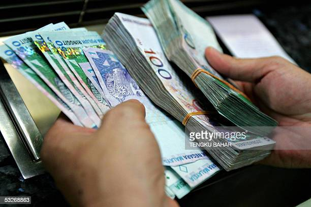 A customer counts ringgit bills in denominations of 1 50 and 100 at the service window of a money changer in Kuala Lumpur 22 July 2005 The Malaysian...