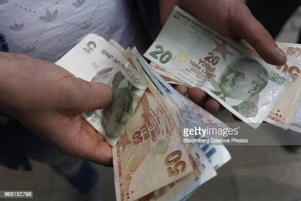 a customer counts turkish lira banknotes - turkish lira stock pictures, royalty-free photos & images