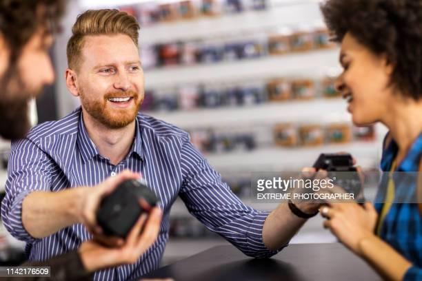 la pareja de clientes que pasa los artículos de nuevo a un vendedor de la tienda en la caja de una tienda de equipos de cámara - devolución del saque fotografías e imágenes de stock