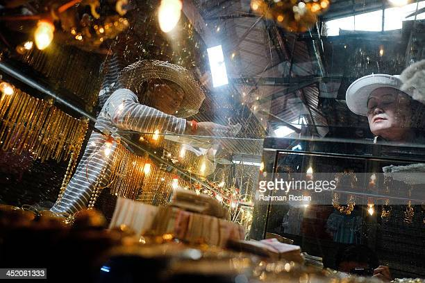A customer deals with a goldsmith at a shop in a wet market on November 26 2013 in Siem Reap Cambodia Cambodian continues their daily life despite a...