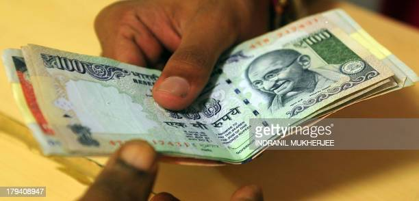 A customer deposits Indian rupee currency notes at a bank in Mumbai on September 3 2013 India's currency slid sharply and the share market crashed...