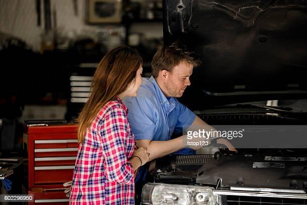 Customer discusses repairs with auto mechanic in repair shop.