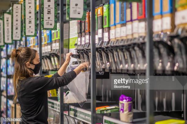 Customer dispenses loose coffee beans into a reusable sack at the 'Refill Zone' inside an Asda store, trialing new sustainability initiatives, in...