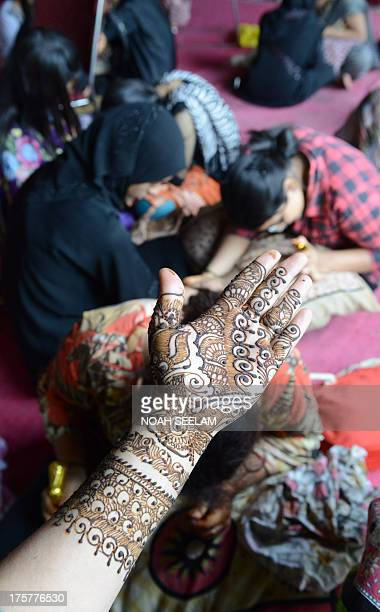 A customer displays her arm styled with mehendi during 'Chand Raat' or 'Night of the Moon' in Hyderabad on August 8 traditionally held on the eve of...