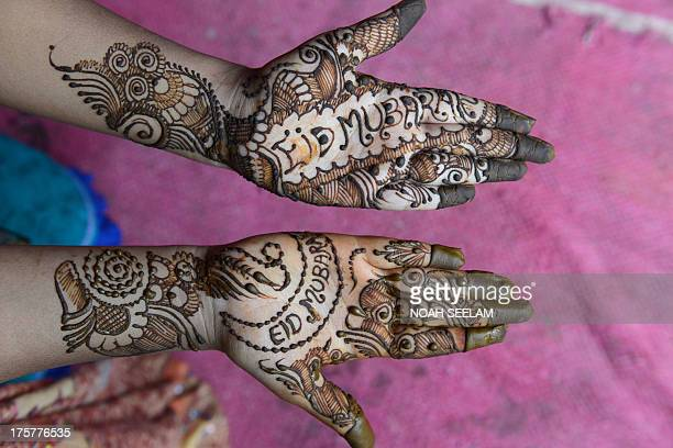 A customer displays her hands styled with mehendi during 'Chand Raat' or 'Night of the Moon' in Hyderabad on August 8 traditionally held on the eve...