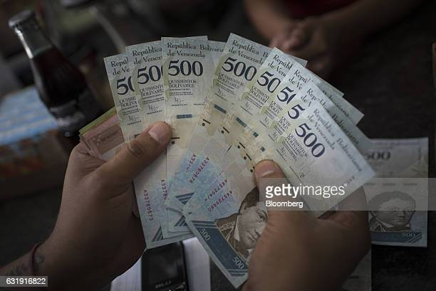 A customer displays new 500 Bolivar banknotes for a photograph while paying at a convenience store in Caracas Venezuela on Tuesday Jan 17 2017 Since...