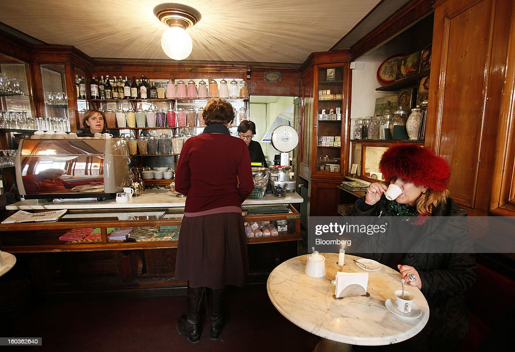 A customer drinks a beverage at a table as another places an order at the counter inside Caffe Bicerin in Turin, Italy, on Tuesday, Jan. 29, 2013. Italy sold 8.5 billion euros ($11.4 billion) of six-month Treasury bills as rates dropped to the lowest in almost three years as the European Central Bank's pledge to buy bonds continues to provide an effective backstop even amid rising political concerns. Photographer: Alessia Pierdomenico/Bloomberg via Getty Images