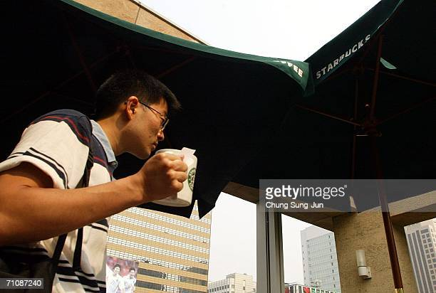 A customer drinks a beverage from Starbucks coffee store on May 31 2006 in Seoul South Korea The National Tax Service has launched its first Tax...