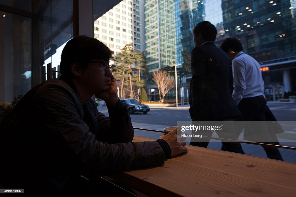 A customer drinks a coffee as pedestrians walk past the Terarosa Coffee shop in Seoul, South Korea, on Tuesday, Feb. 4, 2014. South Korea is Asias fastest-growing market for arabica coffee, the mild-tasting beans used in premium blends. Photographer: SeongJoon Cho/Bloomberg via Getty Images