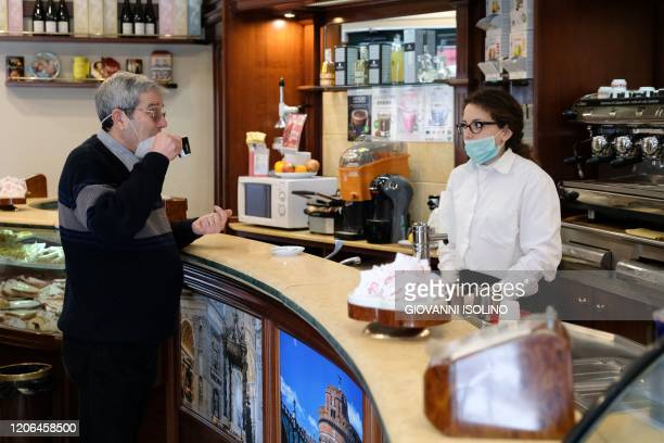 A customer drinks a coffee at a bar in Messina Sicily on March 10 2020 as Italy imposed unprecedented national restrictions on its 60 million people...