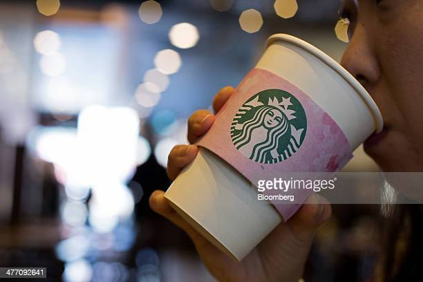 A customer drinks a coffee at a Starbucks Coffee Korea Co store in Gimpo South Korea on Friday March 7 2014 Starbucks Korea's 'returningmom' program...