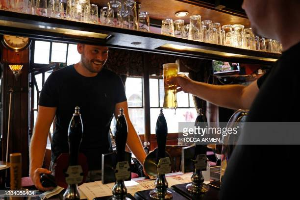 Customer drinks a drink standing at the bar of a pub in central London on July 19, 2021 as coronavirus restrictions are lifted. - England lifts...