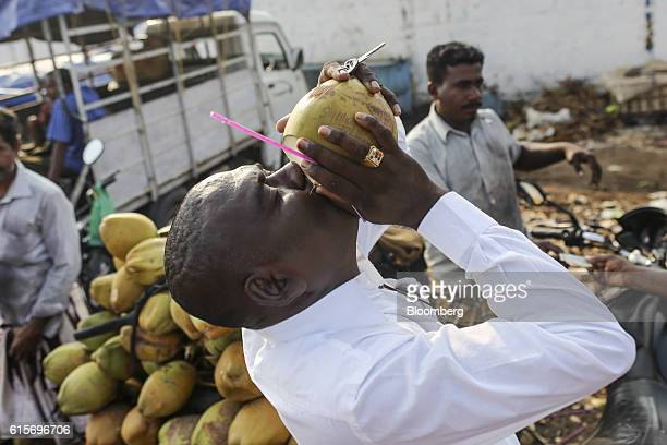 Customer drinks coconut water from a coconut next to a vendor in Nagapattinam, Tamil Nadu, India, on Sunday, Oct. 16, 2016. India's new central bank...