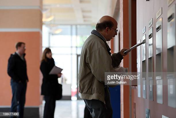 A customer drops letters into a mailbox at the United States Post Office at Rincon Center on December 17 2012 in San Francisco California Customers...