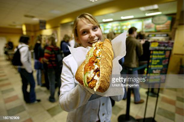 Customer eatinga sandwich in a branch of the US American sandwich fastfood chain Subway