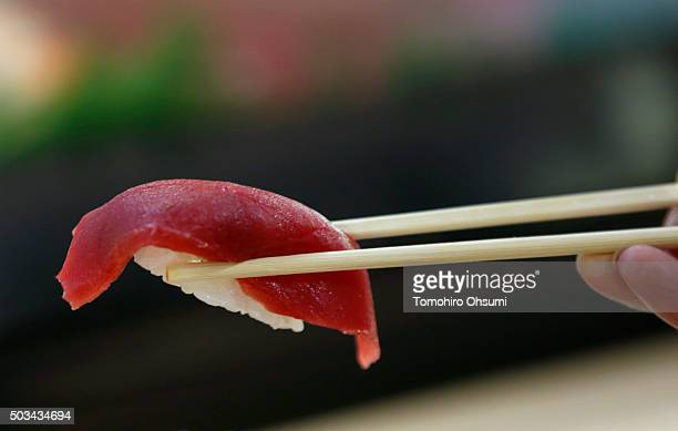 A customer eats a piece of tuna sushi at a Sushi Zanmai sushi restaurant operated by Kiyomura KK after the year's first auction at Tsukiji Market on...
