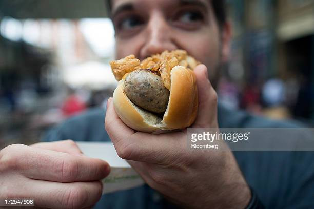 A customer eats a Shake Shack hotdog made with a cumberland sausage outside the company's new burger restaurant in London UK on Tuesday July 2 2013...