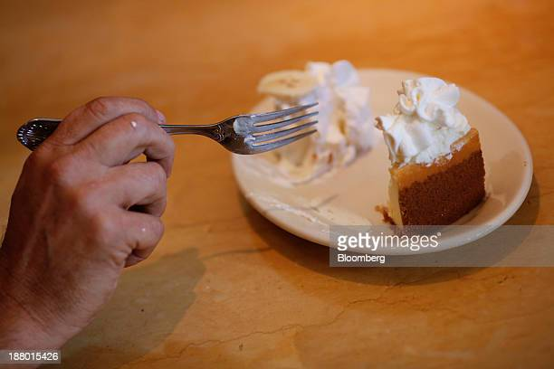 A customer eats a slice of cheesecake for dessert at a Cheesecake Factory Inc restaurant in Louisville Kentucky US on Wednesday Nov 13 2013 Last...