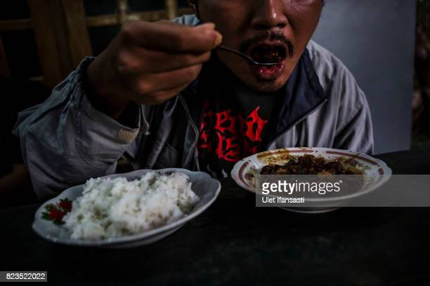 A customer eats dog meat known as 'tongseng' at restaurant specialising in dog meat on July 25 2017 in Yogyakarta Indonesia Indonesians have seen a...
