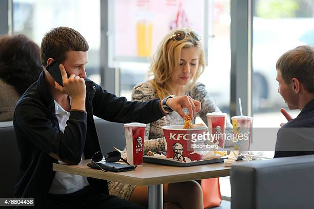 A customer eats fried chicken from a KFC 'bucket' in the new 24hour KFC fast food restaurant operated by Yum Brands Inc in Moscow Russia on Monday...