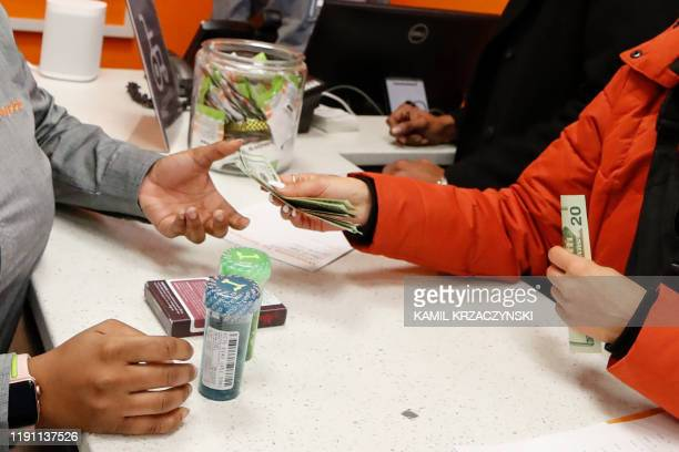 Customer Elise Swopes makes a purchase at Sunnyside Cannabis Dispensary on January 1, 2020 in Chicago, Illinois. - On the first day of 2020,...
