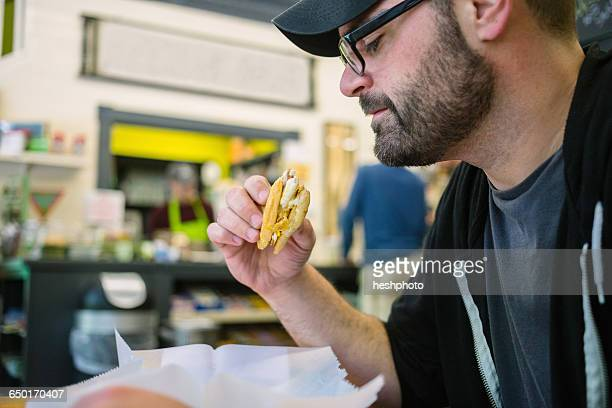 customer enjoying sandwich in general store - heshphoto stock pictures, royalty-free photos & images