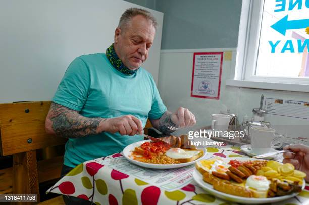 Customer enjoys an early morning Full English Breakfast at an indoor table at Smokey Joe's Cafe, Scorrier, on May 17, 2021 in Falmouth, England....