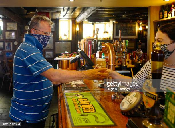 Customer enjoys being able to order his drinks from the bar at the Chainlocker pub on July 19, 2021 in Falmouth, England. As of 12:01 on Monday, July...
