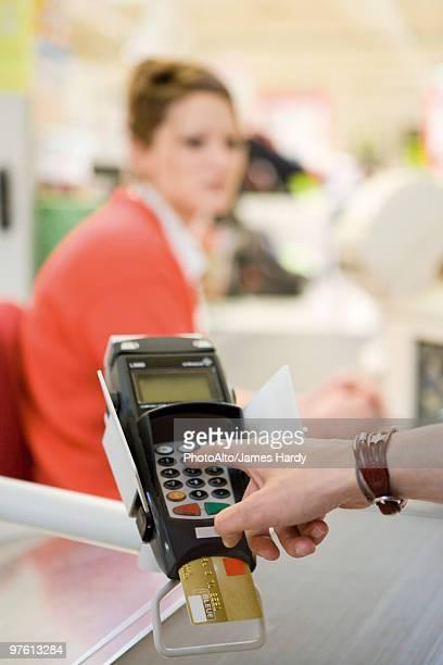 Customer entering pin into credit card reader keypad